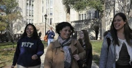 four students walking away from the cathedral of learning
